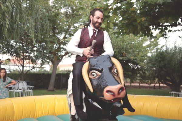 Hombre y niño montados sobre un toro mecánico en una fiesta